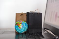 Shopping bags and world globe on laptop keyboard. Worldwide online shopping, e-commerce concept.  royalty free stock photos