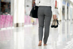 Shopping barefoot. Young woman in office style clothes carrying in hand her high heel shoes, walking barefoot in contemporary building, legs close-up stock photo