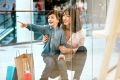 shopping Barnet fostrar och lurar med påsar i galleria royaltyfri bild