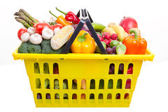 Shopping basket. A yellow shopping basket full of fruits and vegetables isolated on white Royalty Free Stock Photos