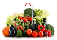 Shopping basket with assorted raw organic vegetables over white Stock Photos