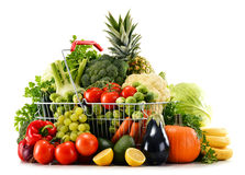 Shopping basket with assorted raw organic vegetables over white Royalty Free Stock Photography
