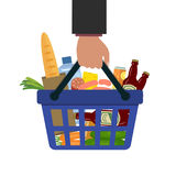 Shopping basket with food and drink in hand. There is a bread, a bottle of water, bottles of beer, sausage, cheese, vegetables and other products in the Stock Photo