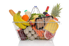 Shopping basket full of fresh food isolated. Wire shopping basket full of groceries including fresh fruit, vegetables, milk, wine, meat and dairy products Stock Photography