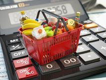 Shopping basket full of grocery foods on calculator. Savings, di Royalty Free Stock Photo