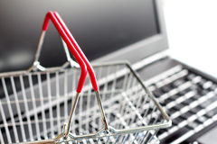 Shopping basket on laptop buying online abstract background concept Stock Photos