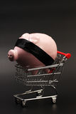 Shopping basket with pink piggy bank with black blindfold inside standing on black background Royalty Free Stock Image