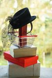 Shopping basket with red purse and small black female hat with veil and feather in retro style. Shopping cart with gift or present royalty free stock photography