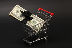Shopping basket with stack of money american hundred dollar bills with black bow inside standing on black background. Horizontal Royalty Free Stock Photos