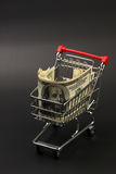 Shopping basket with stack of money american hundred dollar bills inside standing on black background Royalty Free Stock Images