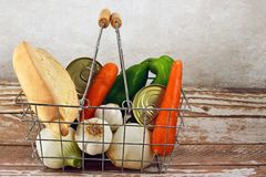 Shopping basket with vegetables, bread and preserves. Still life with bread, garlic, peppers,carrots, onions and preserves Royalty Free Stock Images
