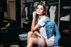 Shopping. Beautiful model brunette girl in stylish clothes, posing in clothing store, a new trend of clothes. Banner for a royalty free stock photography