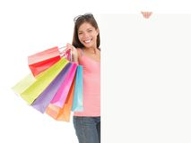 Shopping billboard sign. Shopping woman showing commercial sign. Picture of a beautiful young mixed race woman holding a blank billboard sign while standing stock photography