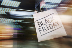 Shopping on Black Friday. Black Friday paperbag carried by hurrying shopaholic Stock Images