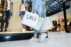 Shopping on black friday. Sale paperbags carried by hurrying shopper choosing new stylish clothes on black friday royalty free stock photo