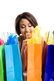 Shopping black woman. An isolated shot of a beautiful black woman looking at her shopping bags Royalty Free Stock Photo