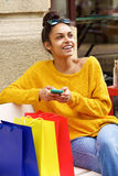 Shopping black woman sitting outdoors on bench Stock Photography