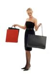 Shopping blond in black dress. Elegant blond with shopping bags over white Stock Photo