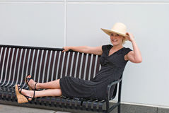 Shopping Break. Blond woman resting on bench with straw hat Stock Photography