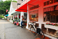 Shopping in Cape Cod. A young woman exits a boutique in downtown Chatham, on Cape Cod Royalty Free Stock Photos