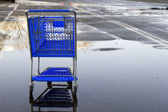 Shopping cart. Lonely shopping cart on the empty parking lot with reflection stock photos