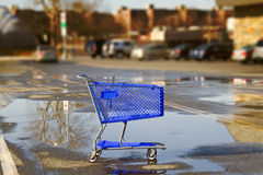 Shopping cart. Lonely shopping cart on the shopping mall parking lot with sky reflection stock photo