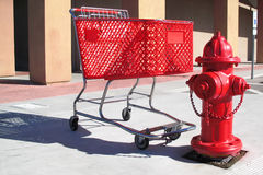 Shopping Cart. Red shopping cart parked next to a red fire hydrant Royalty Free Stock Image
