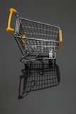 Shopping cart. Image of an empty shopping cart and its shadows against a black background Stock Image