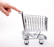 Shopping cart. A hand pushing an empty shopping cart  on white Royalty Free Stock Photo
