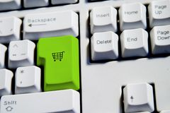 Shopping Cart. Computer Keyboard from a desktop computer with the enter key highlighted in green with a small shopping cart on it Royalty Free Stock Images
