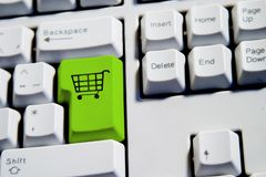 Shopping Cart. Computer Keyboard from a desktop computer with the enter key highlighted in green with a large shopping cart on it Stock Photography