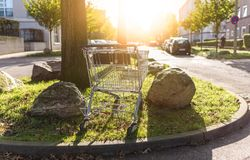 Shopping cart abandoned at curbside in housing area. Shopping cart abandoned at curbside in residential neighborhood Royalty Free Stock Photography