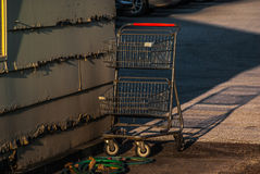 Shopping cart abandoned in a parking lot Stock Photography