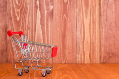 Shopping cart against brown wooden background Stock Photography