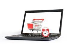 Shopping cart, alarm clock on laptop, close view Stock Photos
