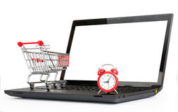 Shopping cart and alarm clock on laptop Royalty Free Stock Photography