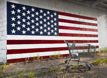 Shopping Cart American Flag. The old shopping cart is sitting on a sidewalk with grass and weeds, with an American flag painted on a concrete block wall behind Royalty Free Stock Photo