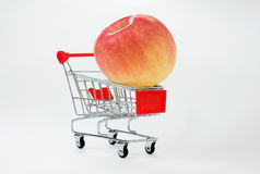 Shopping cart with apple. Apple in shopping basket isolated Royalty Free Stock Images