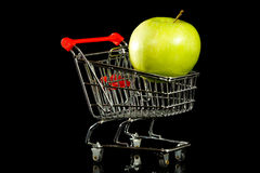 Shopping Cart with Apple. A small toy shopping cart with a green granny smith apple on a black background.    Food or grocery concept Stock Photo