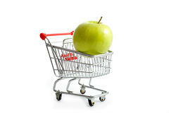 Shopping Cart with Apple. A shopping cart with a green apple, food industry or grocery concept Stock Photos