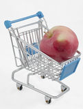 Shopping cart with an apple Royalty Free Stock Photos