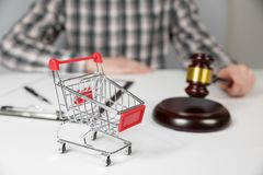 Shopping cart and auction hammer. On the background of a lawyer royalty free stock photo