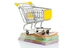 Shopping cart on bills. Shopping cart stands on banknotes, symbolic photo for shopping, purchasing power, money printing and inflation Royalty Free Stock Image