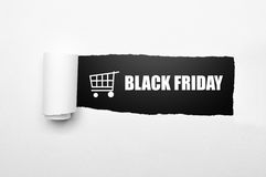Shopping cart and black friday text on paper tear Stock Photography