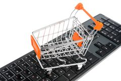 Shopping cart on black keyboard isolated on white Stock Photo