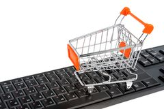 Shopping cart on black keyboard isolated on white Stock Images