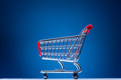 Shopping cart on blue Stock Photo