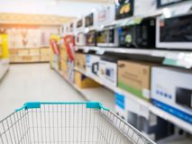 Shopping cart with blur electronics store aisle. Shopping cart with blur microwave shelf in electronics store aisle background stock image