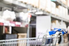 Shopping cart and boxes on rows of shelves in warm light warehouse background. stock images