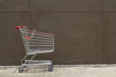 Shopping cart. With brown wall background Stock Photos